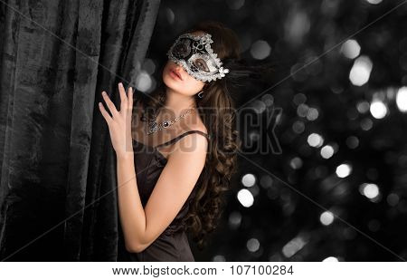 Beautiful woman  in a carnival mask behind the velvet curtain on sparkling dark background.