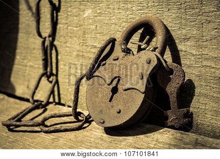 Old rusty metal lock with keys lying on a wooden board.