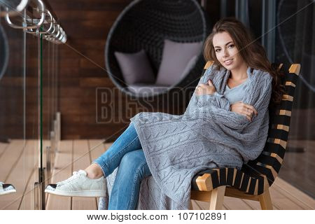 Happy beautiful girl wrapped in gray knitted coverlet sitting on the chair on the balcony