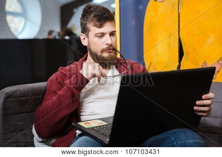 Young handsome man with beard in brown hoodie sitting on sofa, using laptop and holding glasses