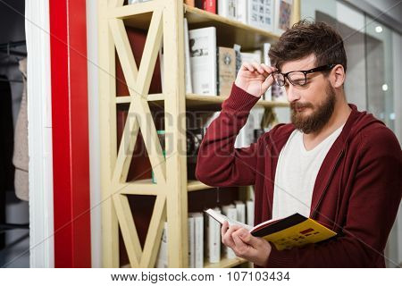 Bearded  young handsome man in brown hoodie and glasses reading book standing near the wooden bookshelf