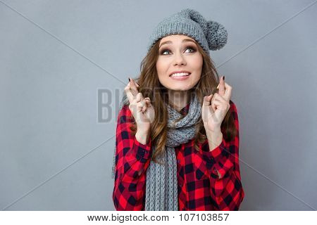 Portrait of a beautiful woman praying with crossed fingers over gray background