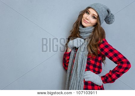 Portrait of a happy woman in winter cloth standing on gray background and looking at camera