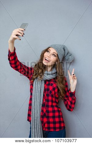Portrait of a smiling woman making selfie photo and showing peace sign with two fingers on gray background