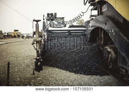 Paver Machinery Laying Fresh Asphalt Or Bitumen During Road Construction On Building Site. Vintage,