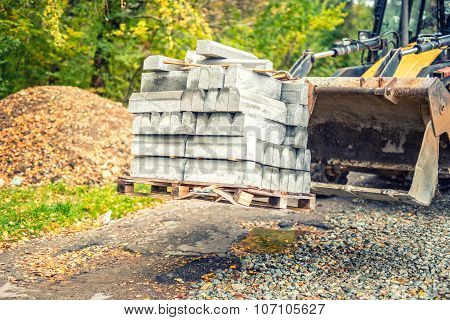 Excavator Or Bulldozer Carrying Pallets With Paving Stones Or Sidewalk Borders