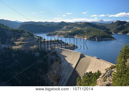Large Dam And Reservoir With Snow Covered Mountains