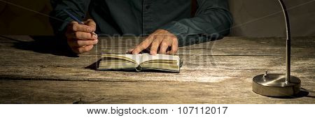 Man Sitting At His Work Desk About To Make A Note In His Notepad