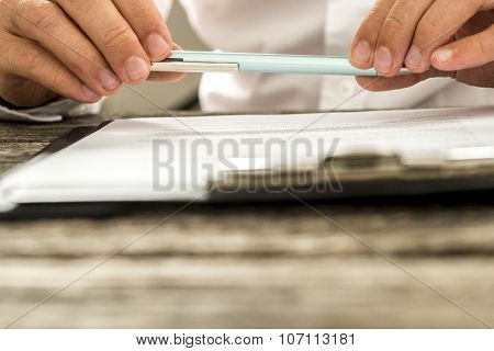 Closeup View Of Male Hands Holding Pencil Over Paperwork On Clipboard As Man Reads Through Terms And