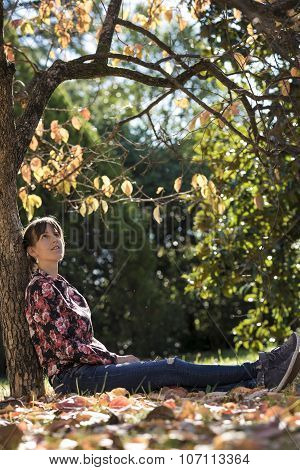 Young Woman Sitting Under Autumn Tree Leaning On Its Trunk