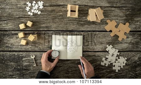 Businessman Making Plan And Business Strategy Decisions As He Sketches A Compass He Is Holding Into