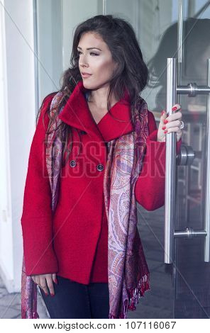 fashionable young woman  wearing red coat and cashmere scarf stand in front glass door, outdoor in the city, autumn day