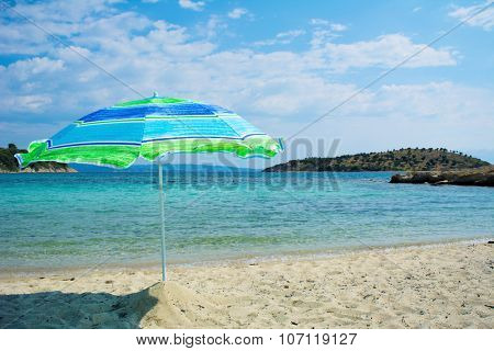 Umbrella on the beach with sea and sky in the background