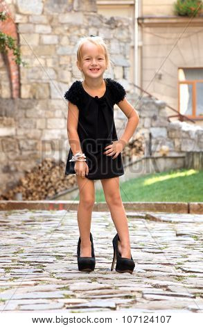 Little Girl Wearing Shoes And Standing On The Road In The City