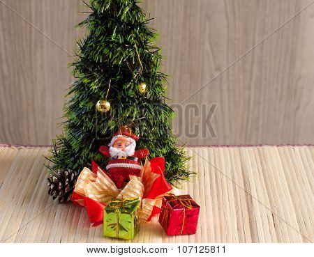 Santa Claus Doll Against A Christmas Tree With Gift Box On Wood Background