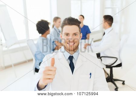 clinic, profession, people, gesture and medicine concept - happy male doctor over group of medics meeting at hospital showing thumbs up gesture