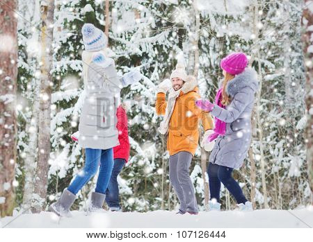 love, season, friendship, entertainment and people concept - group of happy men and women having fun and playing snowballs in winter forest