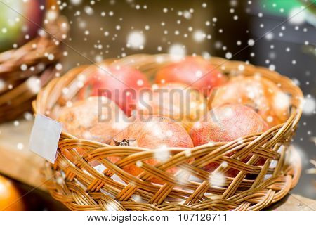 sale, shopping and eco food concept - ripe pomegranates in basket with nameplate at grocery store or market over snow effect