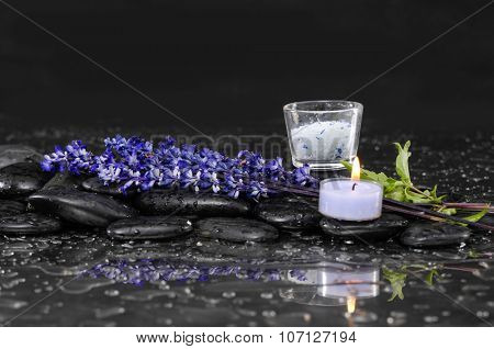 bunch of lavender flower with candle ,salt in glass on wet black stone