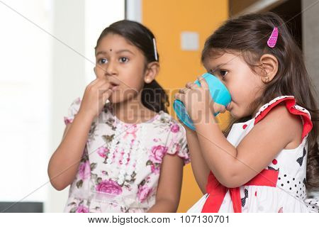 Candid shot of two cute Indian girls eating food and drinking water. Asian sibling or children enjoying tea time food, living lifestyle at home.