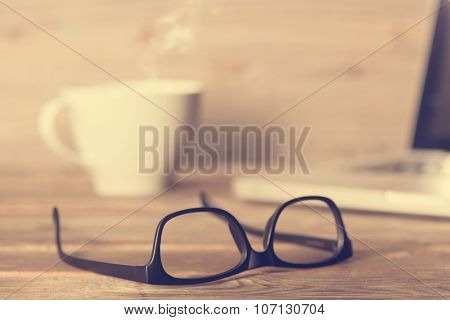 Soft focus wooden work table with glasses, laptop, cup of hot coffee, in dramatic light vintage toned.
