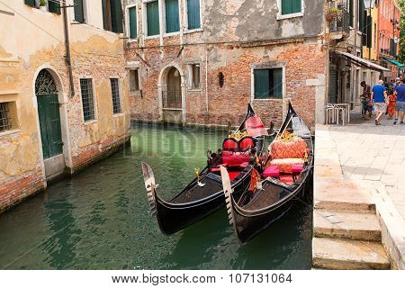 Gondolas Moored By Quay On Venice Canal, Italia.