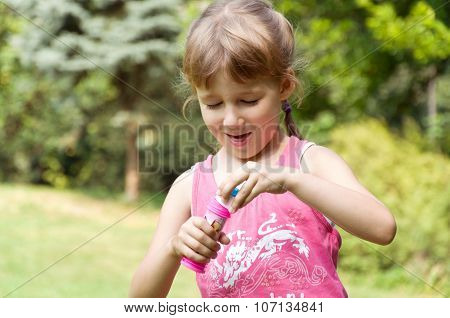 Little Girl In The Park Inflates Soap Bubbles In The Park