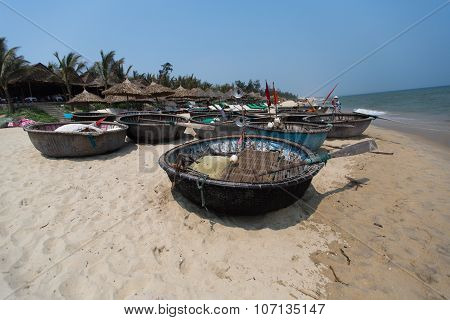 Traditional Fishing Boats On The Beach Of Hoi An City, The Cityscape And Son Tra Peninsulain Are Vis