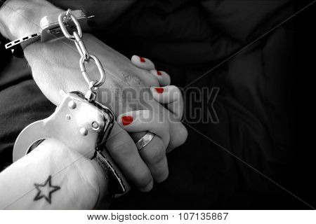 A woman and man's hand handcuffed together