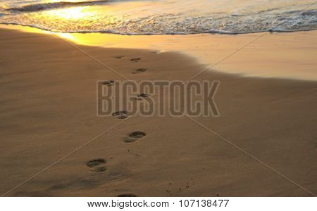 Footsteps leading into the ocean