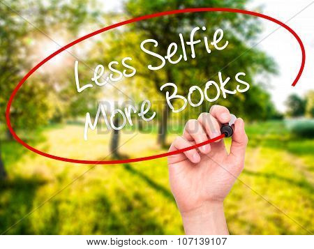 Man Hand writing Less Selfie More Books with black marker on visual screen.