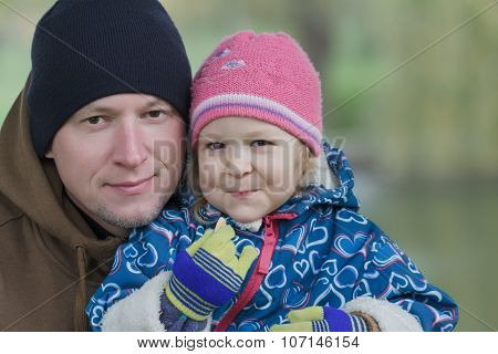 Outdoors Head And Shoulders Portrait Of Father And His Smiling Toddler Daughter