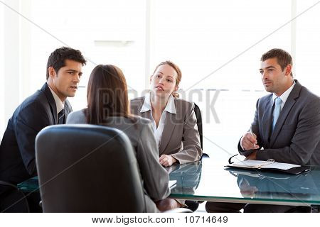 Rear View Of A Businesswoman Being Interviewed By Three Executives