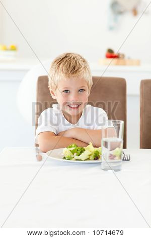 Cute Little Boy Ready To Eat His Salad For Lunch Sitting At A Table