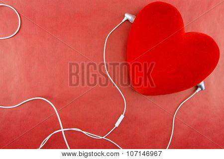 Heart With Earphones Closeup On Red Background