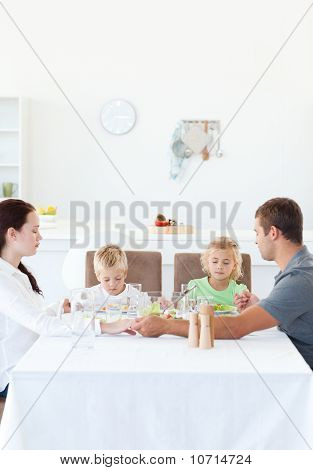 Family Holding Their Hands While Praying Before Eating A Salad