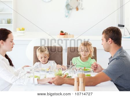 Family Praying Together Before Eating Their Salad For Lunch