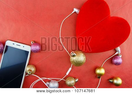Heart With Christmas Ornaments And Smartphone With Earphones, On Red With Copy-space