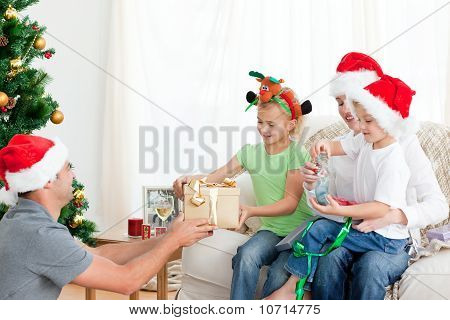 Happy Father Giving A Present To His Daughter Sitting On The Sofa