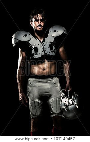 Shirtless American football player with padding holding helmet against black
