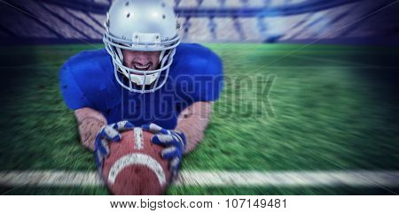 American football player reaching towards ball against rugby pitch