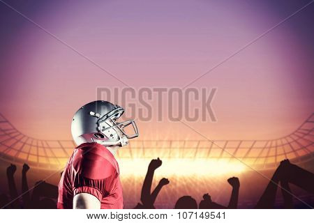 American football player looking up while standing against football stadium with cheering crowd