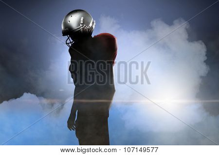 American football player in red jersey looking down against cloudy sky
