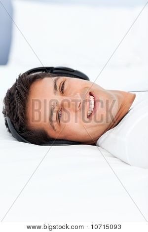 Cheerful Man Listening Music With Headphones Lying On His Bed