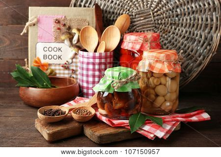 Jars with pickled vegetables, beans, spices and kitchenware on wooden background