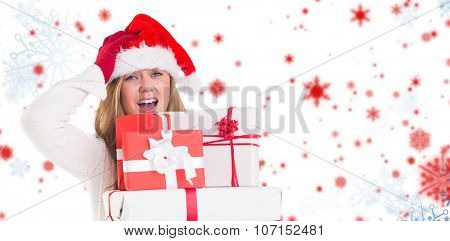 Festive blonde holding pile of gifts against snowflake pattern