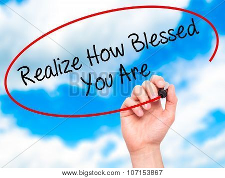 Man Hand writing Realize How Blessed You Are with black marker on visual screen.