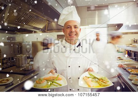 Snow against mature head chef presenting proudly two dinner plates