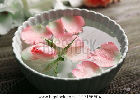 Tender pink rose and petals in a bowl of water on wooden background