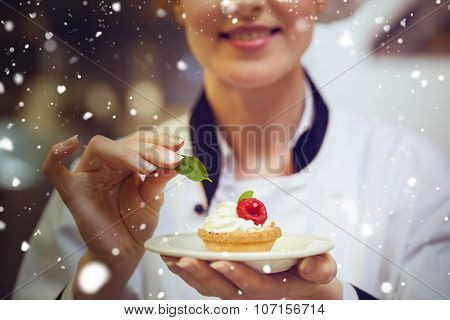 Snow against happy head chef putting mint leaf on little cake on plate